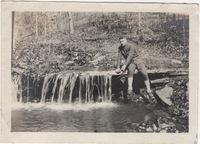John P. Ambuehl sitting next to a waterfall