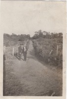Two Men in Civilian Clothes Standing by a Rural Lane