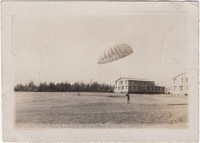 Parachuter Landing in front of Buildings