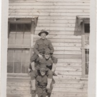 Three Soldiers Sitting on each Other's Shoulders