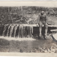 Soldier Sitting next to a Waterfall